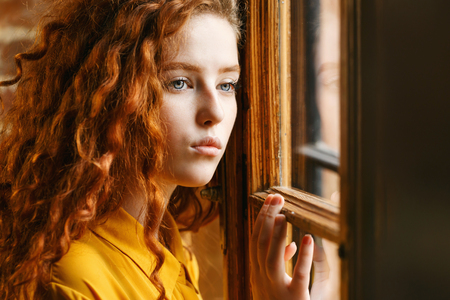 Pensive curly ginger girl in the yellow shirt looking to the window at the loft interior 版權商用圖片