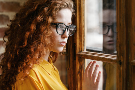 Portrait of pensive curly redhead girl in the yellow shirt wearing glasses looking to the window at the loft placement, the girls face is reflected in the window