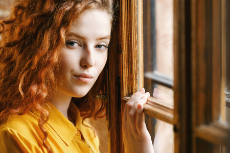 Adorable teen curly ginger girl in the yellow shirt standing near the window and posing to the camera at the loft interior