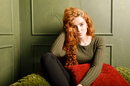 Curly redhead girl relaxing on comfortable soft sofa around the pillows in the green interior 版權商用圖片