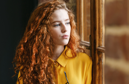 Portrait of curly redhead girl in the yellow shirt looking to the window at the loft placement