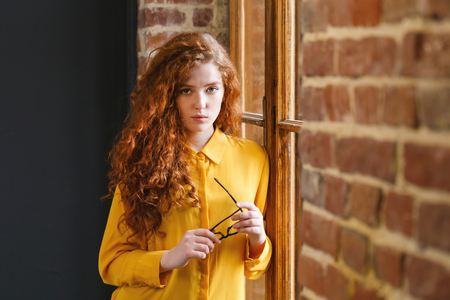 Curly redhead girl in the yellow shirt holding glasses near the window at the loft placement