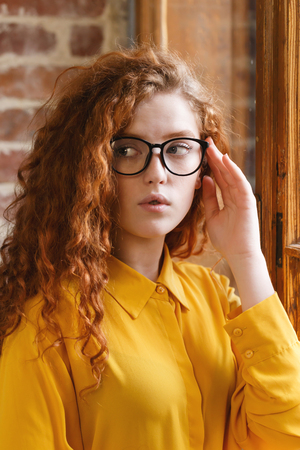 Portrait of curly redhead girl with brackets in the yellow shirt wearing glasses looking away while standing near the window at the loft placement