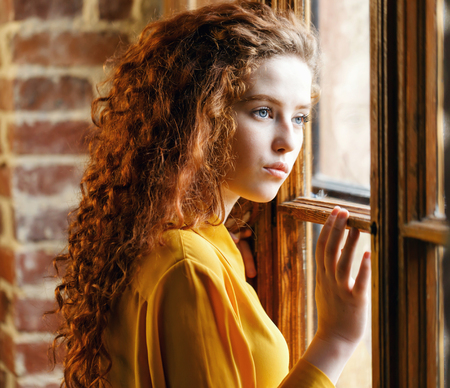 Teen curly ginger girl in the yellow shirt standing near the big wooden window at the loft interior