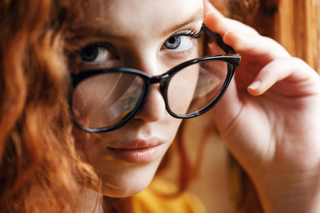 Portrait of teen curly ginger girl in the yellow shirt standing near the big wooden window and looking out of glasses at the loft interior
