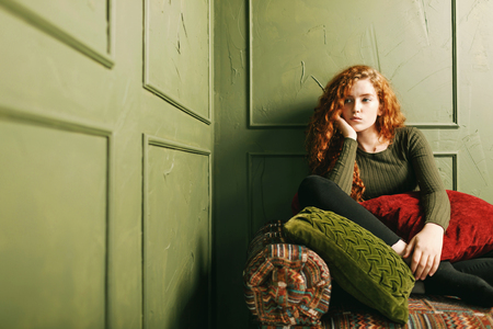 Curly redhead girl looking away while sitting at the sofa around the pillows in the green interior