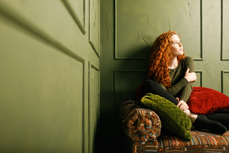 Curly redhead girl looking to the window and sitting at the sofa around the pillows in the green interior 版權商用圖片