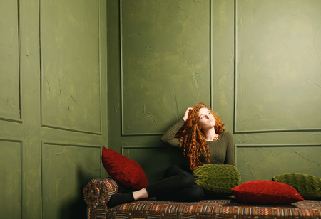 Pensive curly ginger girl dreaming about something while sitting at the sofa around the pillows in the green interior