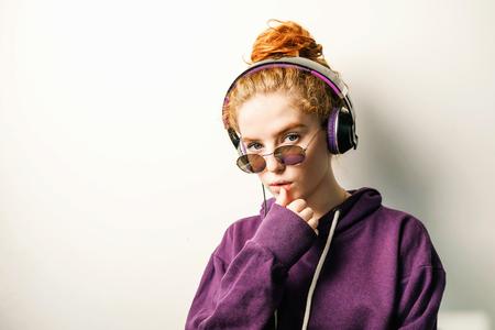 Curly ginger girl in headphones wearing glasses and purple hoodie listening her favorite music