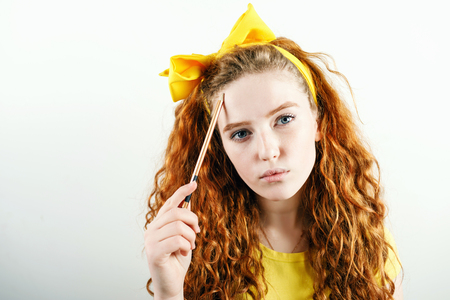 Pensive curly ginger girl with a yellow bow on her head holding pencil near her face and thinking about something while standing on the white background.