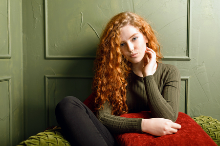 Curly redhead girl sitting at the sofa around the pillows in the green interior