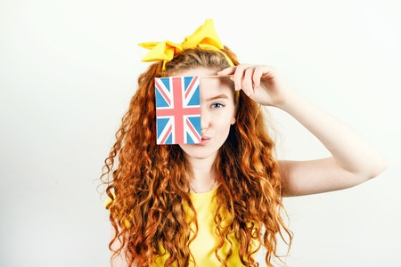 Curly redhead girl with a yellow bow on her head wearing yellow t-shirt hides her face behind the small flag of England while standing on the white background. 版權商用圖片