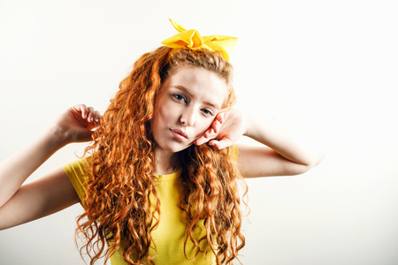 Portrait of curly redhead girl with a yellow bow on her head wearing yellow t-shirt posing on the white background