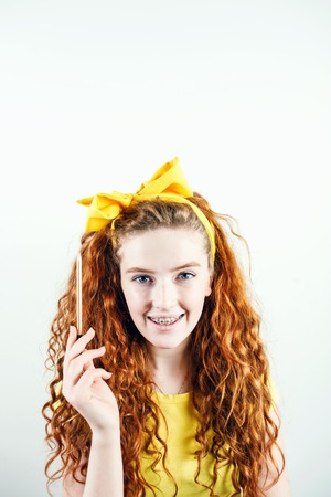 Cheerful curly ginger girl in brackets with a yellow bow on her head standing on the white background and holding pencil up, having idea concept