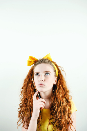 Pensive curly redhead girl with a yellow bow on her head standing on the white background, holding pencil and thinking about something