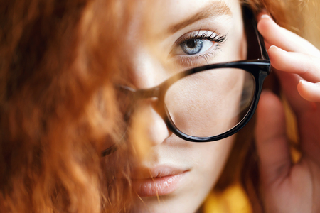 Close up view of teen curly ginger girl in the yellow shirt standing near the big wooden window and looking out of glasses at the loft interior.