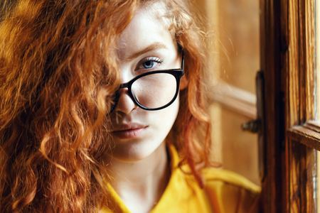 Portrait of teen curly ginger girl in the yellow shirt wearing glasses standing near the big wooden window