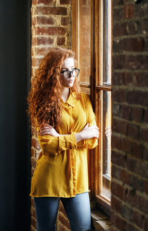 Curly redhead girl in the yellow shirt wearing spectacles standing hands crossed near the big wooden window 版權商用圖片 - 121262787