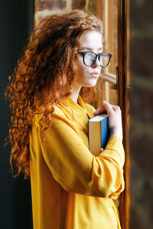 Curly redhead girl in the yellow shirt wearing glasses holding book and looking to the window at the loft placement
