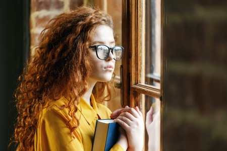 Portrait of curly ginger girl in the yellow shirt wearing glasses holding book and looking to the window at the loft placement