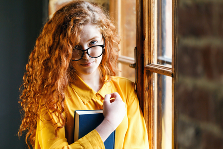 Portrait of curly redhead girl in the yellow shirt wearing eyeglasses holding book and smiling to the camera
