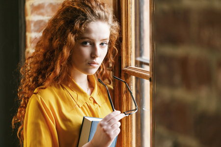 Portrait of curly redhead girl in the yellow shirt holding book and glasses while standing near the window