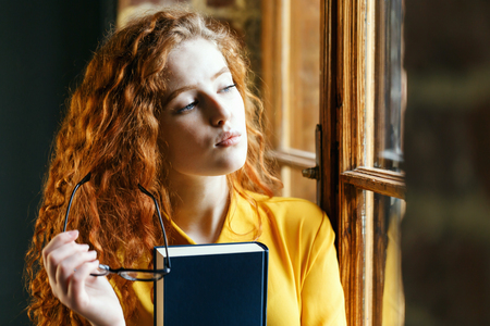Pensive curly redhead girl in the yellow shirt holding book and glasses while looking to the window
