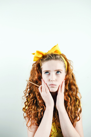 Agitated curly ginger girl with a yellow bow on her head standing on the white background and holding hands near her face