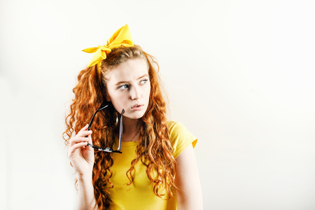 Pensive curly redhead girl with a yellow bow on her head wearing yellow t-shirt holding spectacles and looking away