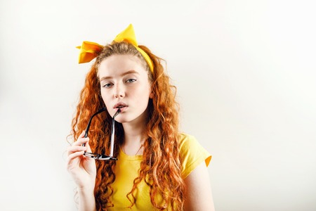 Pensive curly redhead girl with a yellow bow on her head wearing yellow t-shirt holding eyeglasses near her mouth and looking to the camera 版權商用圖片