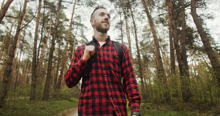 Happy young bearded man dressed in red schecked shirt and backpack walking in the pine forest
