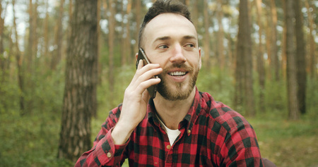 Handsome young bearded man has pleasant talk via smartphone while relaxing in the pine forest