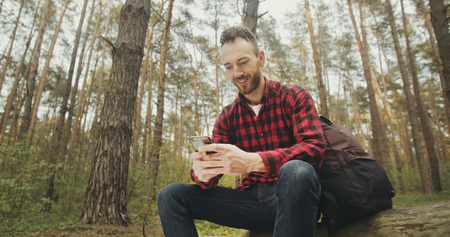 Traveller bearded man using smartphone app while relaxing in the forest