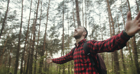 Satisfied young bearded backpacked man dressed in checked shirt breathing healthy in the forest with raised up hands 版權商用圖片