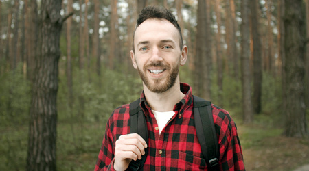 Portrait of young bearded tourist man dressed in red checked shirt with backpack in the forest 版權商用圖片