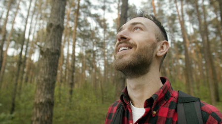 Young bearded man in red checked shirt enjoy pine forest