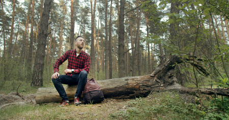 Young backpacked man relaxing on the fallen tree in the forest