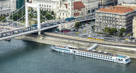 BUDAPEST, HUNGARY - 24 August, 2018: Frame angle view on the Danube River with motor ship and Elisabeth Bridge with many cars