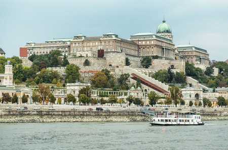 View on Buda Hill among green trees and Danube River on which the ship sails