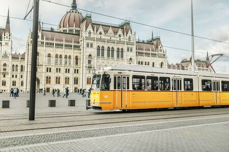 Light rail yellow tram in the city center of Budapest near the Hungarian Parliament Building
