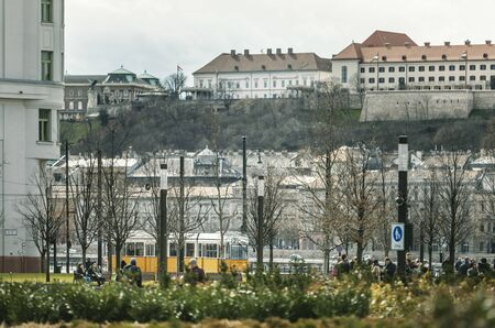 BUDAPEST, HUNGARY - 24 August, 2018: View through the trees to the street of Budapest in which the tram rides and residents walk