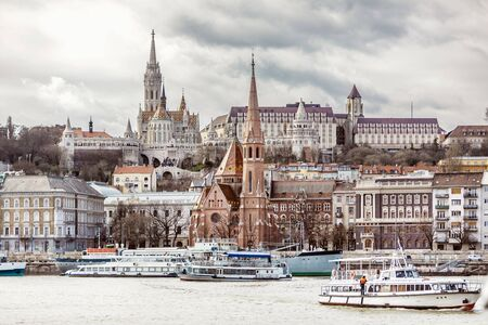 View of Fishermans Bastion and the church of St. Matthias from the east side of Danube with motor ships on it