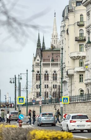 BUDAPEST, HUNGARY - 24 August, 2018: Spring view on the Hungarian Parliament Building of the urban street with cars and people Redakční