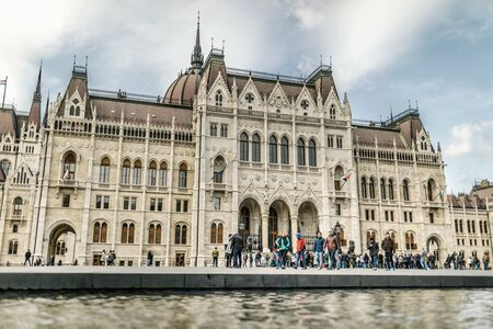 BUDAPEST, HUNGARY - 24 August, 2018: Tourists on the coast of Danube river near the Hungarian Parliament Building Redakční