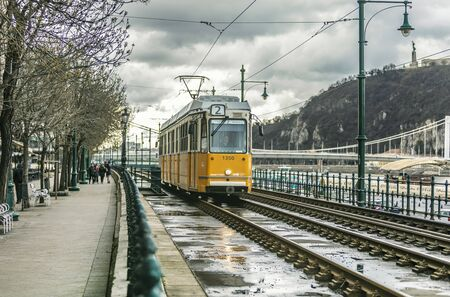 BUDAPEST, HUNGARY - 24 August, 2018: Retro yellow tram in Budapest in Hungary riding on the rails in a on a cloudy spring day 新聞圖片