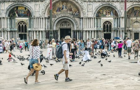 VENICE, ITALY - 25 August, 2018: St Marks Square in Venice with many tourists and pigeons on a spring warm day