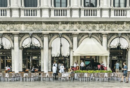 VENICE, ITALY - 25 August, 2018: View on the italian restaurant wit tourists and musicants on the St Marks Square in Venice Redakční