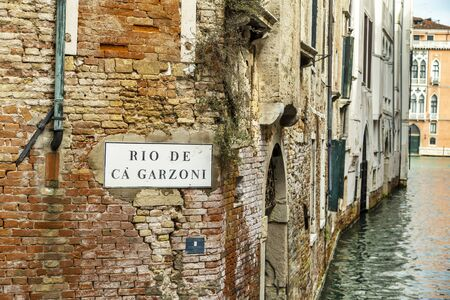 VENICE, ITALY - 25 August, 2018: View of the Rio de Garzoni Canal and brick wall of ancient building in Venice, Italy