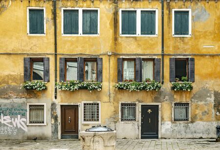VENICE, ITALY - 25 August, 2018: Typical venetian street view on the building with yellow plaster