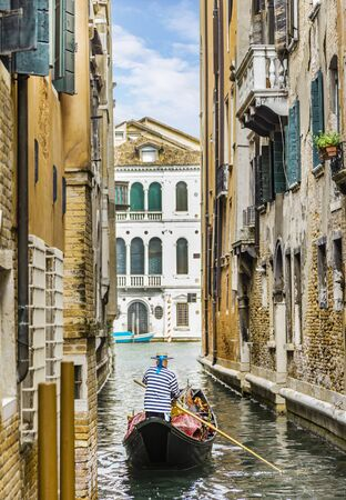 Gondolier in a stripped vest floating on a gondola through a narrow channel among the houses in Venice Archivio Fotografico